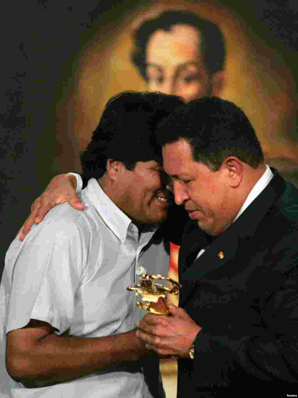 Bolivian President-elect Evo Morales (L) receives a replica of South American independent fighter Simon Bolivar's sword from Venezuelan President Hugo Chavez at the Miraflores Palace in Caracas January 3, 2006. Morales is in Venezuela for a one-day visit. REUTERS/Jorge Silva