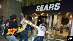Участники беспорядков разбивают дверь магазина. Ванкувер, 15 июня 2011 года.