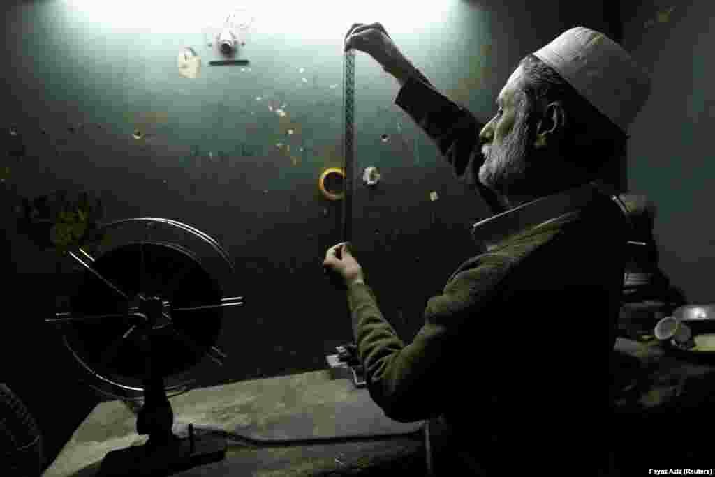 An employee checks a strip of film at a cinema in Peshawar, Pakistan. (Reuters/Fayaz Aziz)
