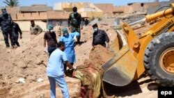 Iraqi officers and forensics team personnel dig at a site believed to be a mass grave in Ramadi, April 19, 2016