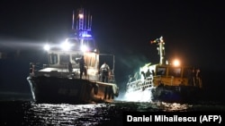 A border police ship pulls a vessel transporting migrants the port of Midia on the Black Sea coast on September 13.