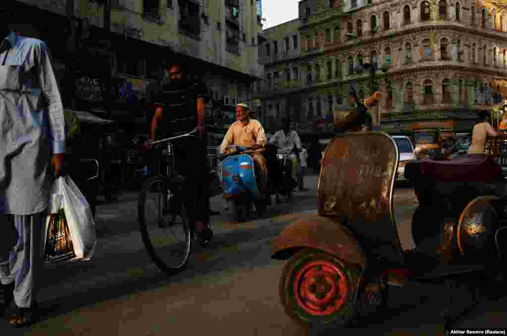 A Vespa rider weaves through traffic in a working class neighborhood of Karachi.