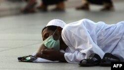 Бетіне тұмаудан қорғанатын маска тағып алған қажылыққа келген мұсылман. Мекке, Сауд Арабиясы, 12 қараша 2009 жыл