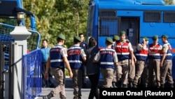 Түркияда полиция Фетхулла Гүленмен байланысы бар деп айыпталған сарбазды ұстап әкетіп барады. Қазан 2017 жыл.