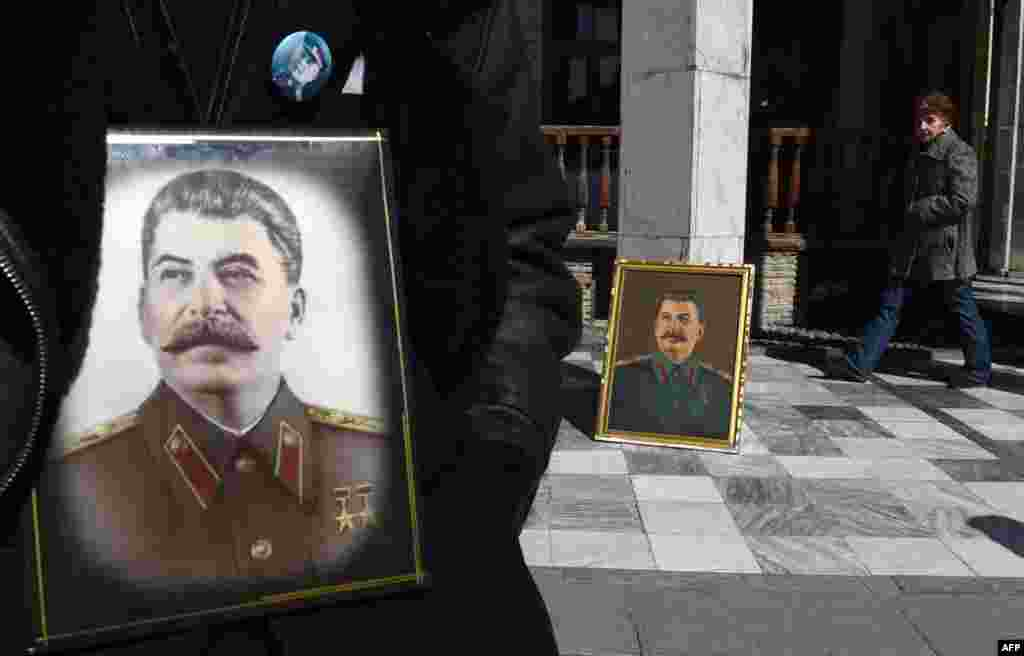 Portraits of Soviet dictator Josef Stalin outside a museum in his native town of Gori, some 80 kilometers outside Tbilisi, on the 64th anniversary of his death. While historians blame Stalin for the deaths of millions in purges, prison camps, and forced collectivization, many in Russia still praise him for leading the Soviet Union to victory over Nazi Germany in World War II. (AFP/Vano Shlamov)