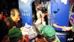 Policët e largojnë një kolegë të plagosur jashtë aeroportit të Karaçit pas sulmit të militantëve më 8 qershor