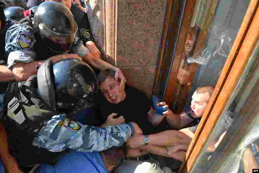 Ukrainian riot police officers stop an opposition deputy as he tries to enter the building of the Kyiv City Council through a window. The opposition lawmakers have been blocking council sessions for months, demanding that elections for the Kyiv City Council and the Kyiv mayor's office be held this year. (AFP/Vitali Lazebnyk)