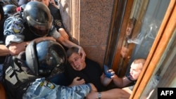 Ukrainian riot police officers stop an opposition deputy as he tries to enter the building of the Kyiv City Council through a window.
