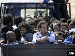 Попавших в плен боевиков Муаммара Каддафи увозят на грузовике отряда временного правительства Ливии. Сирт, 20 октября 2011 года.