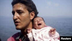 A Syrian refugee from Aleppo holds his 1-month-old daughter moments after arriving on a dinghy on the Greek island of Lesbos on September 3.