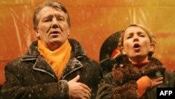 Кандидат в президенты Украины Виктор Ющенко и его политический соратник Юлия Тимошенко поют гимн Украины на Майдане Незалежности. Киев, 29 ноября 2004 года.