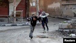 Fëmijë sirianë vrapojnë rrugëve për të evituar snajperistët në Deir al-Zor, 16 shkurt, 2014
