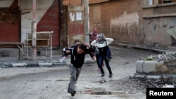 Children run across a street to avoid snipers in Deir al-Zor, Syria, earlier this year. A Britain-based nongovernmental organization says nearly 8,000 children have died in Syria's civil war.