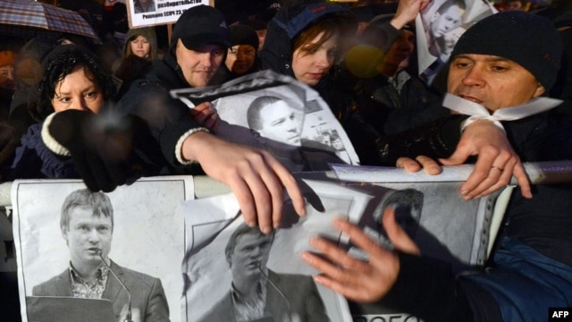 Russian opposition activists hold posters bearing portraits of a jailed opposition activist Leonid Razvozzhayev during a rally in central Moscow last month.