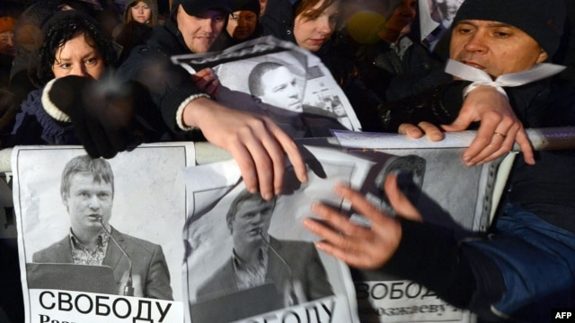 Opposition supporters hold posters bearing portraits of detained opposition activist Leonid Razvozzhayev during a rally in central Moscow on October 30.