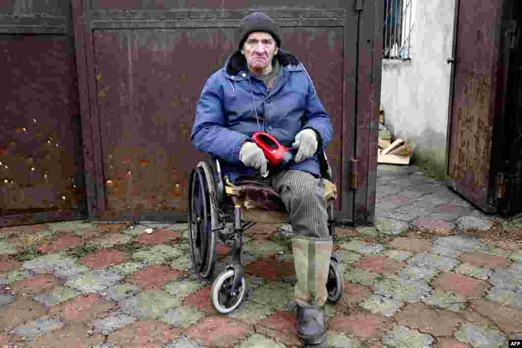 Viktor Gudelya, who lost a leg in shelling in 2014, watches firemen battle a blaze after his house in Avdiyivka was destroyed as a result of heavy shelling by Russia- backed rebels on February 26. (AFP/Anatolii Stepanov)