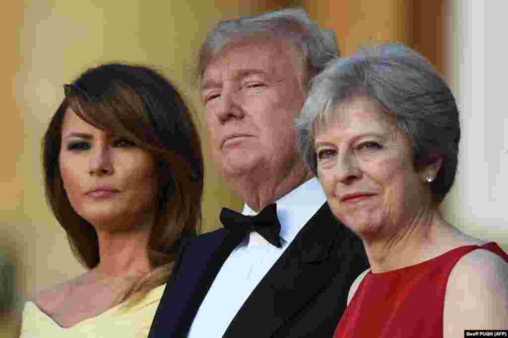 U.K. -- (L-R) US First Lady Melania Trump, US President Donald Trump and Britain's Prime Minister Theresa May stand on steps in the Great Court as the bands of the Scots, Irish and Welsh Guards perform a ceremonial welcome as they arrive for a black-tie d