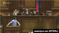 Opposition lawmaker Gevork Petrosian (at the podium) and Parliament Speaker Ararat Mirzoyan (in the center on the tribune) during a heated exchange over an initiative to ban same-sex marriages. November 12, 2019