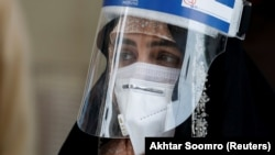 A woman wears a protective face shield and a protective face mask as she attends an event of mask distribution along a road, as the outbreak of the coronavirus disease (COVID-19) continues in Karachi, Pakistan on June 15.