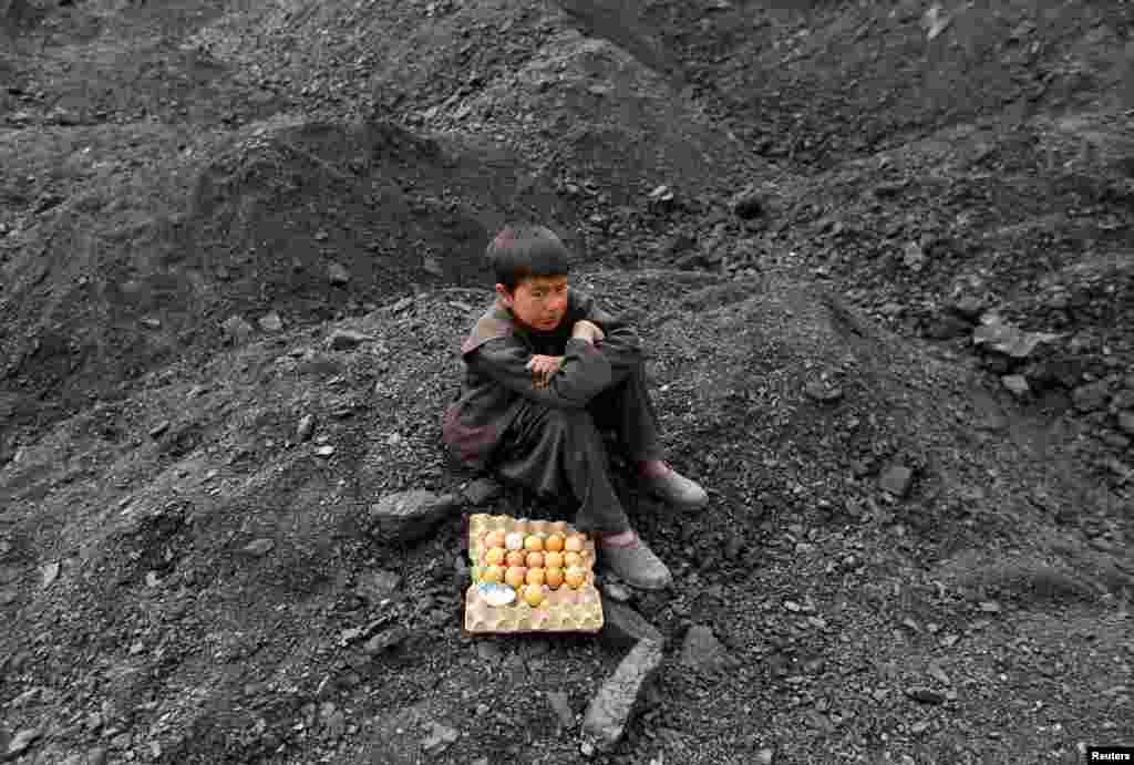 An Afghan boy selling boiled eggs waits for customers at a coal dump site on the outskirts of Kabul. (Reuters/Mohammad Ismail)