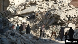 People walk past the rubble of damaged buildings in a rebel-held area of Aleppo on November 6.