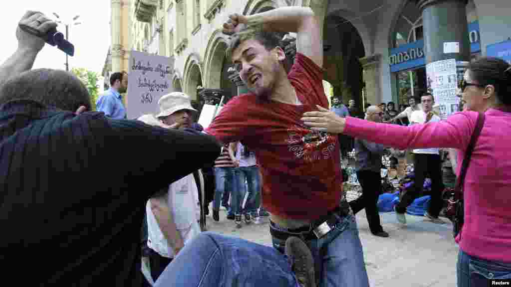 A gay rights activist (right) clashes with an Orthodox Christian activist in Tbilisi during the rally