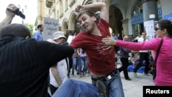 A gay rights activist clashes with an Orthodox Christian activist in Tbilisi on May 17, 2012.