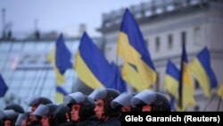 Riot police stand guard during a rally to support EU integration in central Kyiv on November 22.