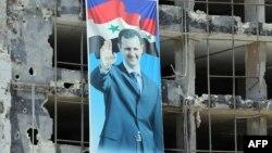 Портрет президента Башара Асада на одном из разрушенных зданий в Хомсе
