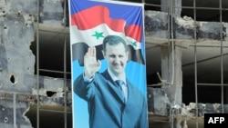 Suriyada döyüşlərdə xaraba qalmış yayaış binalarından birində prezident Bashar al-Assad-ın seçki portreti. 3 iyun 2014.