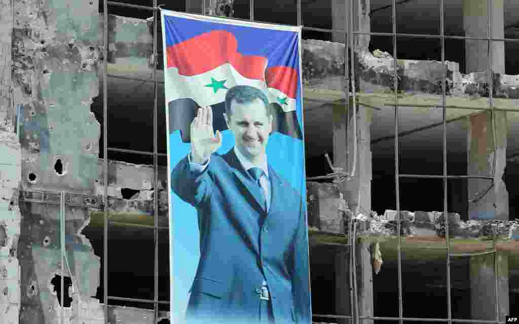 A banner with a picture of Syrian President Bashar al-Assad hangs on a destroyed building in the Homs neighborhood of Khaldiyeh. (AFP/Joseph Eid)