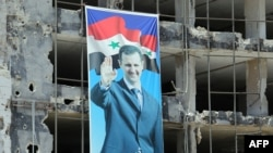 A banner with a picture of President Bashar Assad hangs on a destroyed building in the Homs neighborhood of Khaldiyeh.