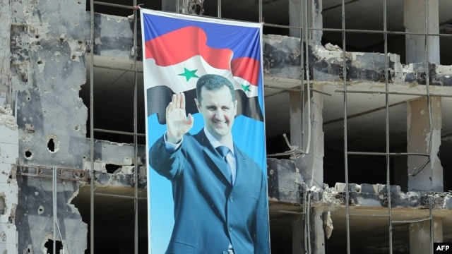 Syria -- A banner with a picture of President Bashar Assad hangs on a destroyed building in the Homs neighborhood of Khaldiyeh, June 3, 2014