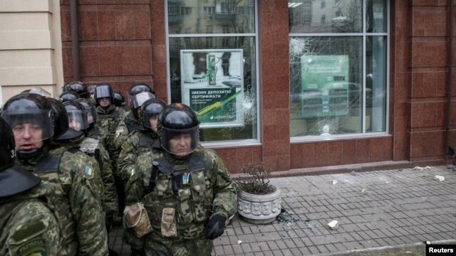 Ukrainian Interior Ministry troops stand guard outside a branch of Russian bank Sberbank, which was attacked on February 20.