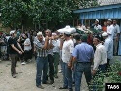 Люди несут тело убитой Натальи Эстемировой на кладбище в 70 км от Грозного 17 июля 2009