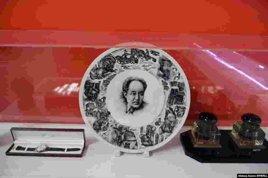 Интересный подарочный набор. В центре – фарфоровое блюдо спортретом Мухтара Ауэзова в центре и образами из его произведений покраям. Слева – часы марки «Полет» в футляре. Справа, видимо, чернильницы.