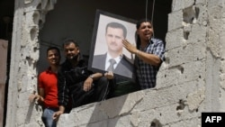 Syria -- Syrians in a damaged building hold up a portrait of their President Bashar al-Assad as UN observers inspect a nearby Shiite holy shrine in the Sayyida Zeinab suburb of Damascus, after a suicide car bomb exploded there, 14Jun2012