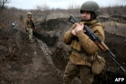 Ukrainian soldiers patrol along a position at the front line with Russia-backed separatists not far from Avdiyivka in the Donetsk region on April 5.