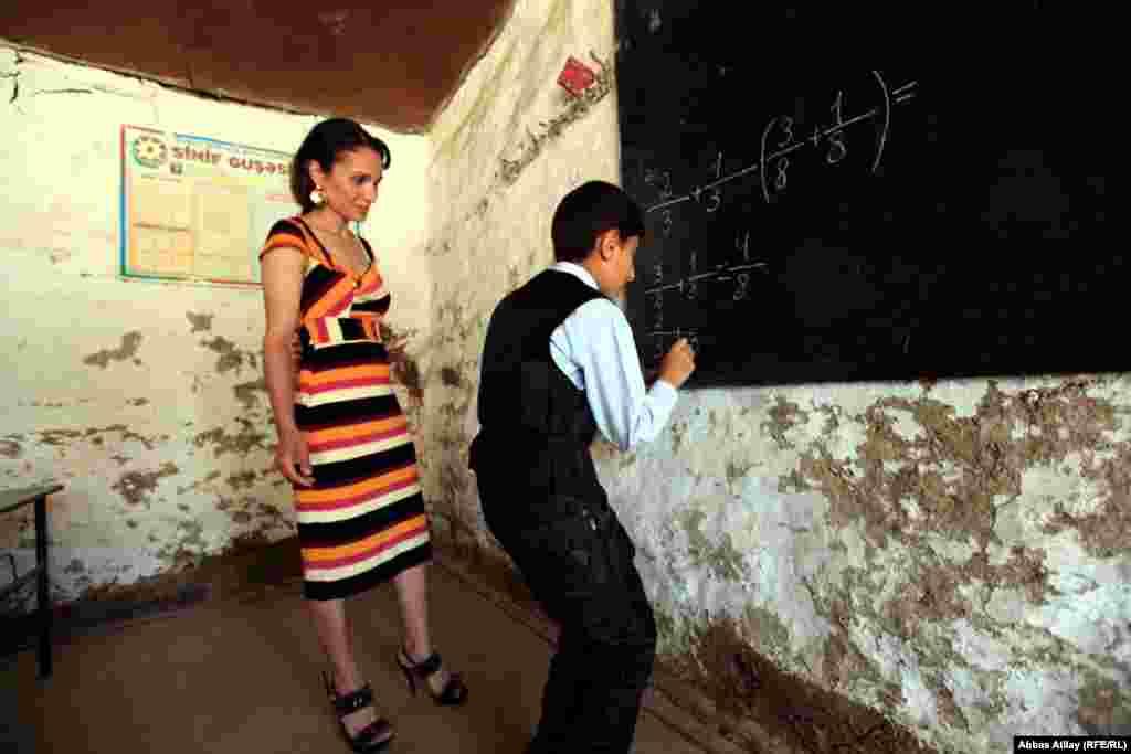 A teacher monitors math class in a Jalilabad school.