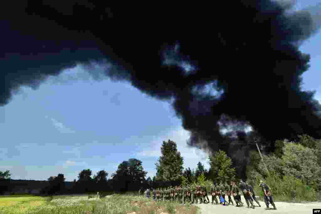 Dark smoke billows from a fire at a fuel depot as Ukrainian servicemen walk past in the village of Kryachki, some 30 kilometers southwest of Kyiv. The blaze killed five people, including three firemen. (AFP/Sergei Supinsky)