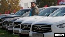 Мінілген қымбат көліктерді қарап жүрген адам. Мәскеу, 12 қыркүйек 2014 жыл.