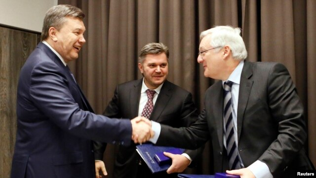 Eduard Stavytskyi, chairman of Ukraine's state geology and mineral resources service (center), watches as Ukrainian President Viktor Yanukovych (left) shakes hands with Peter Voser, CEO of Royal Dutch Shell in Davos, on January 24.