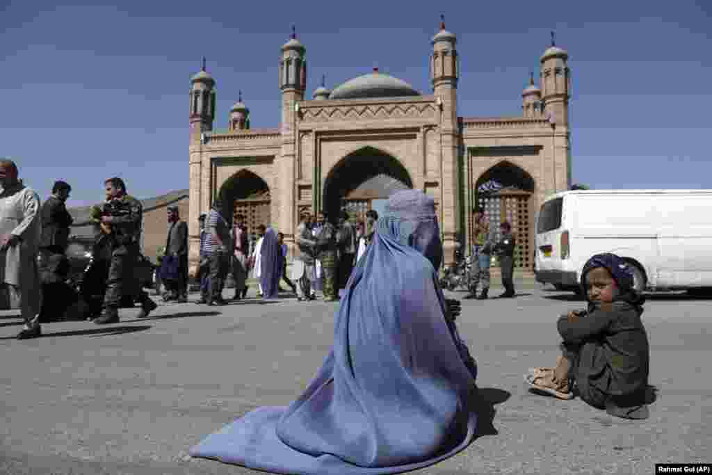 An Afghan woman waits for alms during the first day of Eid al-Fitr in Kabul, Afghanistan.