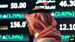 A Saudi man walks at the Tadawul Saudi Stock Exchange, in Riyadh, Saudi Arabia, Monday, June 15, 2015. Saudi Arabia's stock market, valued at $585 billion, opened up to direct foreign investment for the first time Monday, as the kingdom seeks an economic