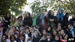 Иранские женщины наблюдают отдельно от мужчин за уличным футболом.