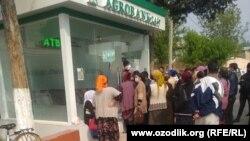 Люди стоят в очереди за наличными деньгами возле филиала «Агробанка» в Чартакском районе Наманганской области, 7 апреля 2020 года.