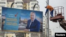 Рабочий красит столб рядом с билбордом с изображением действующего президента и кандидата в президенты Казахстана Нурсултана Назарбаева. Алматы, 14 апреля 2015 года.