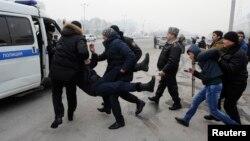 Задержанных на площади Республики участников акции протеста против одномоментной девальвации силой ведут в полицейскую машину. Алматы, 15 февраля 2014 года.