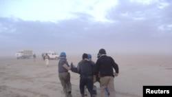 شماری از ساکنان اردوگاه اشرف در حال حمل یک زخمی، پس از حمله نیروهای عراقی. ۸ آوریل ۲۰۱۱.
