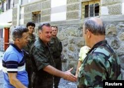 Comandatul sârbilor bosniaci, (stânga) îi strânge mâna unuia dintre soldații săi în Srebrenica, după ce au pus mâna pe enclavă pe 11 iulie.
